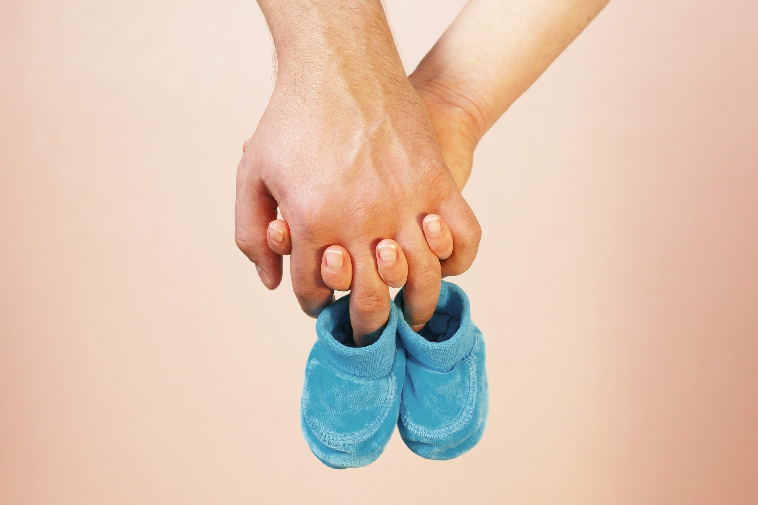 Couple holding hands with baby booties