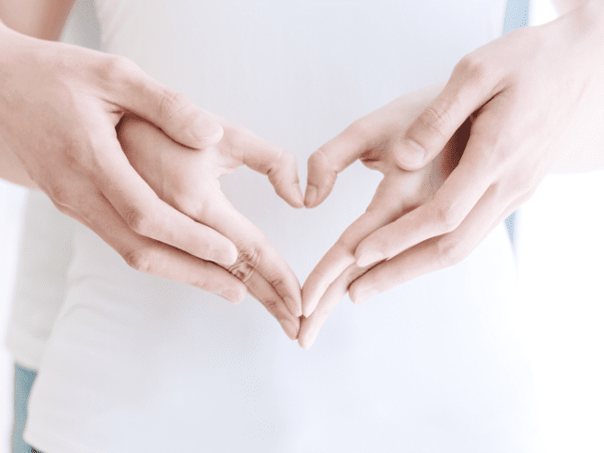 couple holding hands in heart shape