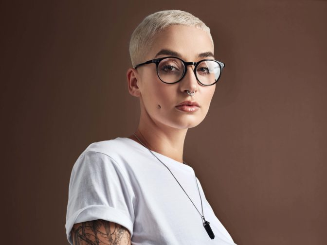young woman with glasses, white T-shirt and tattoos