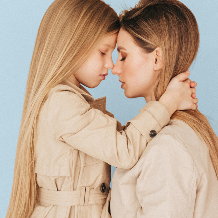 Woman and young girl touch foreheads